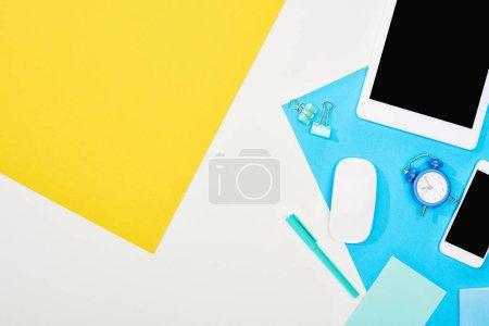Photo pour Smartphone de vue supérieure, tablette numérique avec écran blanc et souris d'ordinateur avec des fournitures de bureau sur fond jaune, bleu et blanc - image libre de droit
