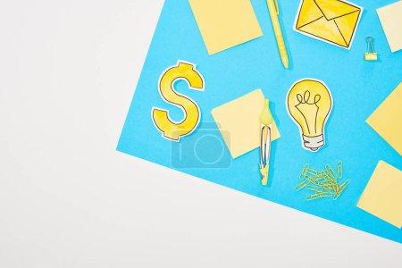 Photo pour Vue du dessus du lieu de travail avec fournitures de bureau jaunes, icônes en papier sur fond bleu et blanc - image libre de droit