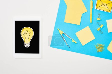 Photo for Top view of workplace with office supplies and digital tablet with light bulb icon on blue and white background - Royalty Free Image