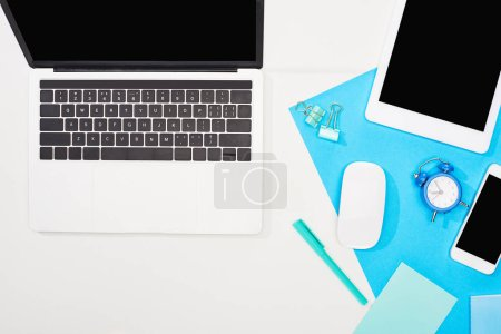 top view of gadgets with blank screen on blue and white background