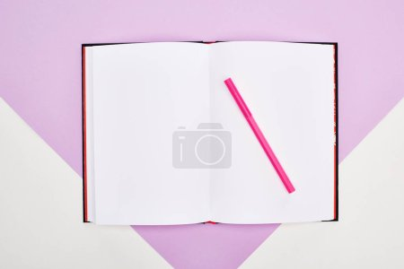 Photo for Top view of open empty notebook with felt pen on violet and white background - Royalty Free Image