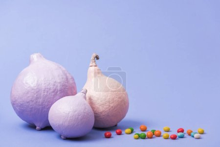 Photo for Festive painted pumpkins with candies on violet background - Royalty Free Image