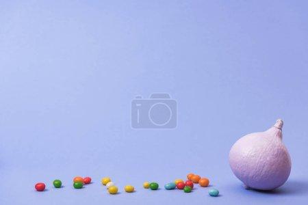 Photo pour Citrouille peinte festive avec des bonbons sur fond violet - image libre de droit