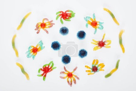 top view of colorful gummy spiders and worms isolated on white, Halloween treat