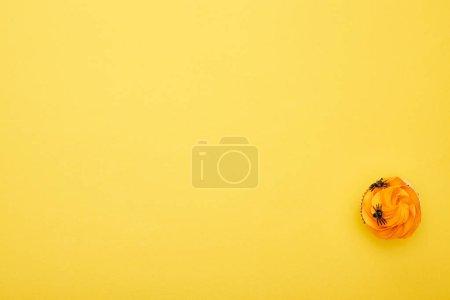 Foto de Vista superior de cupcake naranja con arañas en el fondo amarillo, regalo de Halloween - Imagen libre de derechos