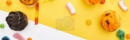 Photo for Panoramic shot of colorful gummy sweets and cupcakes on yellow and white background, Halloween treat - Royalty Free Image