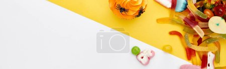 Photo for Top view of colorful gummy sweets and cupcakes on yellow and white background, Halloween treat - Royalty Free Image