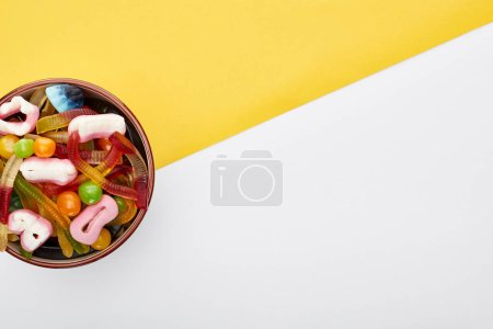 Photo for Top view of colorful gummy sweets in bowl on yellow and white background, Halloween treat - Royalty Free Image