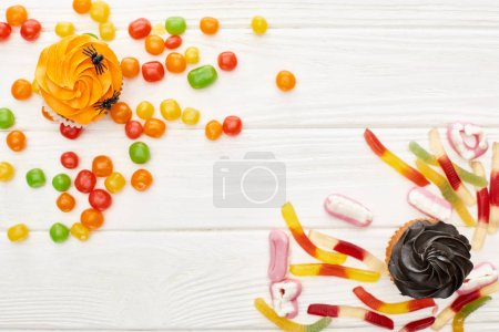 Photo for Top view of colorful gummy sweets, cupcakes and bonbons on white wooden table, Halloween treat - Royalty Free Image