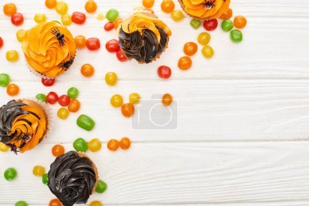 Photo for Top view of colorful bonbons and cupcakes on white wooden table, Halloween treat - Royalty Free Image