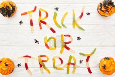 Photo for Top view of trick or treat lettering made of colorful gummy sweets on white wooden table with spiders and cupcakes, Halloween treat - Royalty Free Image
