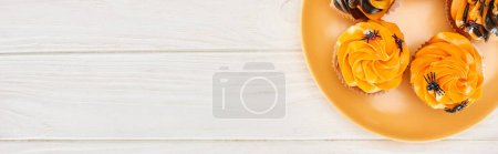 Photo for Top view of delicious cupcakes with spiders on orange plate on white wooden table, Halloween treat - Royalty Free Image