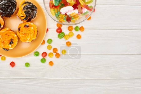 Photo for Top view of colorful gummy sweets, bonbons and cupcakes on white wooden table, Halloween treat - Royalty Free Image