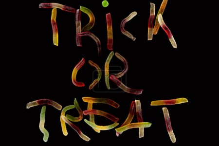 top view of colorful trick or treat lettering made of gummy worms isolated on black, Halloween treat