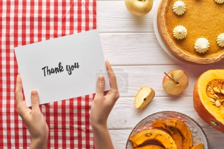 Photo for Partial view of woman holding thank you card near pumpkin pie on wooden white table with apples - Royalty Free Image