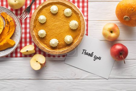top view of traditional pumpkin pie with thank you card on wooden white table with apples