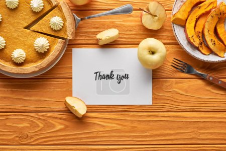 Photo for Top view of delicious pumpkin pie, apples and thank you card on wooden orange table - Royalty Free Image