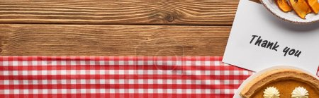 Photo for Top view of tasty pumpkin pie and thank you card on wooden rustic table with plaid napkin, panoramic shot - Royalty Free Image