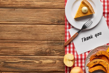 Photo for Top view of tasty pumpkin pie, apples and thank you card on wooden rustic table with plaid napkin - Royalty Free Image