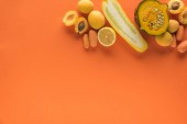 """Постер, картина, фотообои """"top view of yellow fruits and vegetables on orange background with copy space"""""""