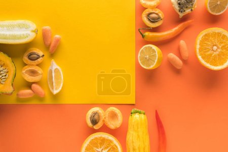 Photo for Top view of delicious fruits and vegetables on yellow and orange background with copy space - Royalty Free Image