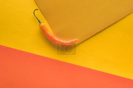 top view of yellow spicy pepper yellow and orange background with copy space