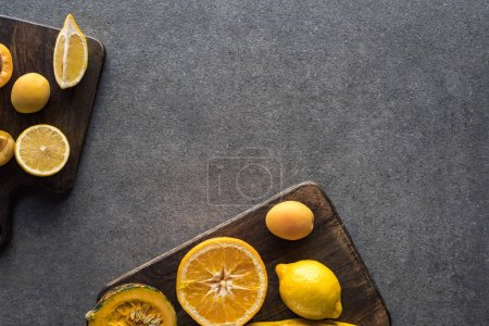 Photo for Top view of yellow fruits and vegetables on wooden cutting boards on grey textured background with copy space - Royalty Free Image