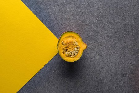 top view of pumpkin on yellow and grey background