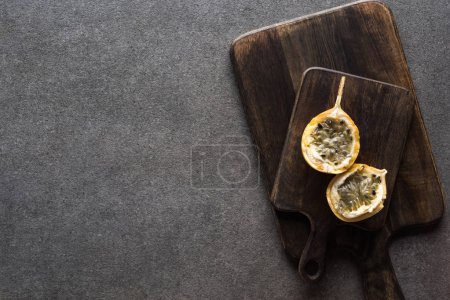 top view of sweet granadilla on wooden cutting boards on grey background