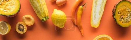 Foto de Vista superior de las frutas y hortalizas amarillas sobre fondo naranja, tiro panorámico. - Imagen libre de derechos