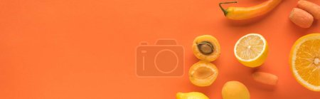 Foto de Top view of yellow fruits and vegetables on orange background with copy space, panoramic shot - Imagen libre de derechos