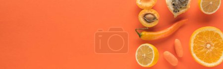 Photo for Top view of yellow fruits and vegetables on orange background with copy space, panoramic shot - Royalty Free Image