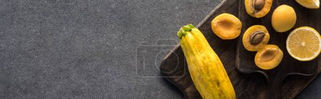 Photo for Top view of yellow fruits and vegetables on wooden cutting boards on grey textured background, panoramic shot - Royalty Free Image