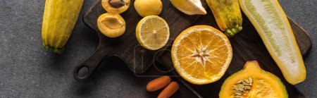 top view of yellow fruits and vegetables on wooden cutting boards on grey textured background, panoramic shot