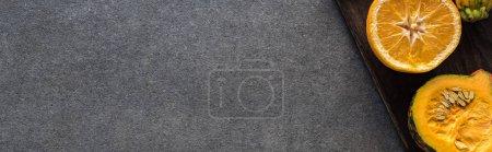 Photo pour Vue du dessus de l'orange et de la citrouille sur des planches à découper en bois sur fond gris texturé, vue panoramique - image libre de droit