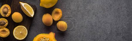 Photo for Top view of pumpkin, apricots and lemon on wooden cutting boards on grey textured background, panoramic shot - Royalty Free Image