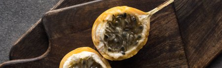 top view of sweet granadilla on wooden cutting boards on grey background, panoramic shot