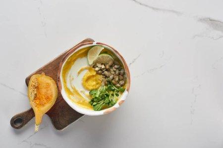 vue du dessus de la soupe automnale à la purée de citrouille dans un bol sur une planche à découper en bois avec citrouille sur une surface en marbre