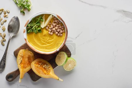 Photo for Top view of autumnal mashed pumpkin soup in bowl on wooden cutting board near pumpkin, seeds, lime and spoon on marble surface - Royalty Free Image