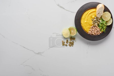 Photo for Top view of autumnal mashed pumpkin soup in bowl near pumpkin seeds and lime on marble surface - Royalty Free Image