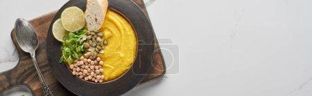 vista superior de sopa de calabaza molida otoñal en tazón sobre tabla de cortar de madera con cuchara en superficie de mármol, plano panorámico