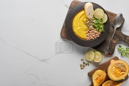 top view of autumnal mashed pumpkin soup in bowl on wooden cutting board on marble surface