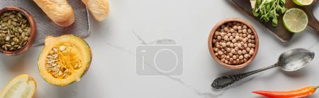 Photo for Top view of pumpkin, seeds, silver spoon, bread and chickpea on marble surface, panoramic shot - Royalty Free Image