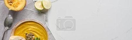 Draufsicht auf herbstliche Kürbissuppe auf Marmoroberfläche in der Nähe von Silberlöffel und Limette, Panoramaaufnahme