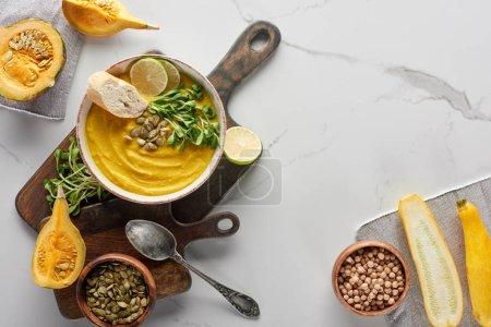 Photo pour Vue d'ensemble de la soupe aux citrouilles en purée de saison sur une planche à découper en bois avec ingrédients sur une surface de marbre - image libre de droit