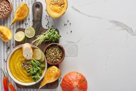 Ansicht der saisonalen pürierten Kürbissuppe auf Holzschneidebrett mit Zutaten auf Marmoroberfläche