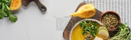 Photo for Top view of autumnal mashed pumpkin soup on wooden cutting board on marble surface, panoramic shot - Royalty Free Image