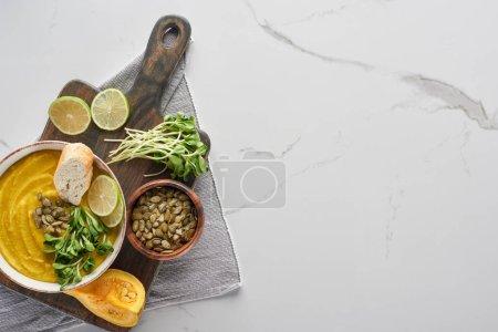 Photo pour Vue de dessus de la délicieuse soupe à la citrouille écrasée sur planche à découper en bois sur la surface de marbre avec des ingrédients - image libre de droit
