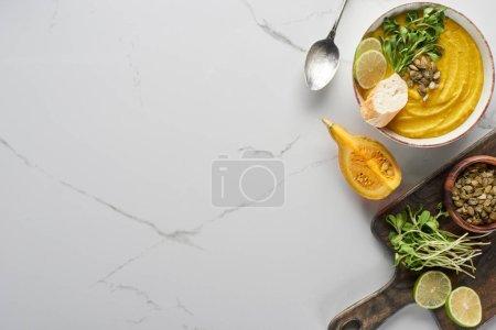 Photo pour Vue du dessus de la délicieuse soupe à la citrouille en purée sur une planche à découper en bois sur une surface de marbre avec ingrédients - image libre de droit
