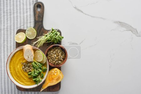 top view of tasty mashed pumpkin soup on wooden cutting board with ingredients on marble surface